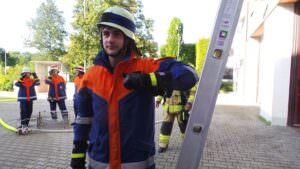 Die Steckleiter ist aufgebaut, Sebastian prüft, ob die Leiter korrekt steht.